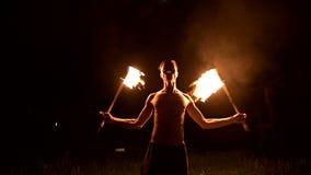 Низкий ключ Молодой мужчина с длинными волосами и обнаженным торсом поворачивает горящий outdoors факела на замедленном движении  сток-видео