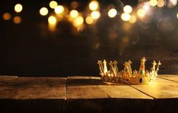 низкий ключ ферзя/кроны короля над деревянным столом Фильтрованный год сбора винограда период фантазии средневековый Стоковое фото RF