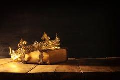 низкий ключ ферзя/кроны короля на старой книге Фильтрованный год сбора винограда период фантазии средневековый стоковая фотография