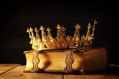 низкий ключ ферзя/кроны короля на старой книге Фильтрованный год сбора винограда период фантазии средневековый стоковое изображение rf