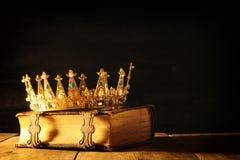 низкий ключ ферзя/кроны короля на старой книге Фильтрованный год сбора винограда период фантазии средневековый Стоковое фото RF