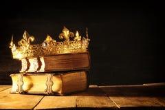 низкий ключ ферзя/кроны короля на старых книгах Фильтрованный год сбора винограда период фантазии средневековый Стоковые Изображения RF