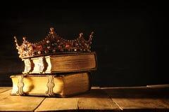 низкий ключ ферзя/кроны короля на старых книгах Фильтрованный год сбора винограда период фантазии средневековый Стоковые Фотографии RF