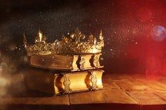 низкий ключ красивых ферзя/кроны короля на старых книгах Фильтрованный год сбора винограда период фантазии средневековый стоковые фотографии rf