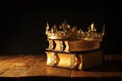 низкий ключ красивых ферзя/кроны короля на старых книгах Фильтрованный год сбора винограда период фантазии средневековый Стоковые Изображения RF