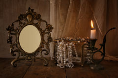 Низкий ключ пустой винтажной рамки, жемчугов на деревянном столе Стоковые Изображения