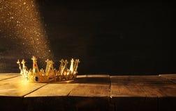 низкий ключ ферзя/кроны короля над деревянным столом Фильтрованный год сбора винограда период фантазии средневековый Стоковое Изображение RF