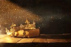 низкий ключ ферзя/кроны короля на старой книге Фильтрованный год сбора винограда период фантазии средневековый Стоковая Фотография RF