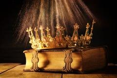 низкий ключ ферзя/кроны короля на старой книге Фильтрованный год сбора винограда период фантазии средневековый стоковые фото