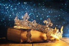 низкий ключ ферзя/кроны короля на старой книге Фильтрованный год сбора винограда период фантазии средневековый Стоковое Фото