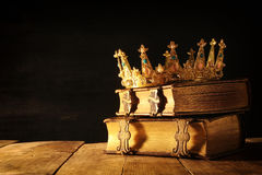 низкий ключ ферзя/кроны короля на старых книгах Фильтрованный год сбора винограда период фантазии средневековый стоковое изображение rf