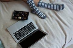 Низкий раздел женщины ослабляя с шоколадами и компьтер-книжкой на кровати Стоковые Изображения RF