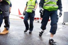 Низкий раздел работников идя на влажное взлётно-посадочная дорожка Стоковое Изображение