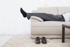 Низкий раздел бизнесмена отдыхая на софе в живущей комнате Стоковые Фото