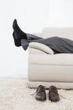 Низкий раздел бизнесмена отдыхая на софе в живущей комнате Стоковое фото RF