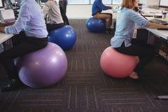 Низкий раздел бизнесменов сидя на шариках тренировки пока работающ на офисе стоковые фото