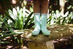 Низкий раздел девушки нося зеленый резиновый ботинок стоя на каменном стенде Стоковое Фото