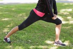 Низкий раздел женщины делая протягивая тренировку в парке Стоковые Фотографии RF