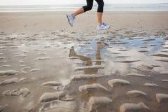 Низкий раздел здоровой женщины jogging на пляже Стоковые Изображения