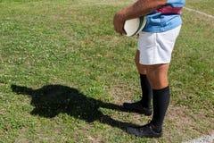 Низкий раздел игрока рэгби держа шарик на поле Стоковые Изображения