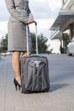 Низкий раздел коммерсантки стоя с багажом на подъездной дороге Стоковые Изображения