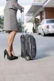 Низкий раздел коммерсантки стоя с чемоданом на подъездной дороге Стоковые Изображения RF
