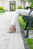Низкий раздел молодой женщины ослабляя на скамейке в парке Стоковая Фотография