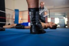 Низкий раздел мужского боксера стоя против рефери спортсменом Стоковые Фото
