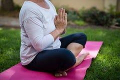 Низкий раздел старшей женщины размышляя в положении молитве Стоковая Фотография RF