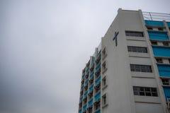 Низкий угол здания со стальным крестом на предпосылке неба overcast стоковое фото rf