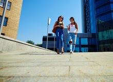 Низкий угол зрения камеры снял 2 женских друзей идя вдоль st Стоковые Фотографии RF