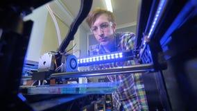Низкий угол человека наблюдая процесс печатания в принтере 3d 4K акции видеоматериалы