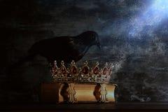 низкое ключевое изображение красивых ферзя/кроны короля и черной вороны период фантазии средневековый Селективный фокус Стоковые Изображения RF