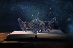 низкое ключевое изображение красивых ферзя/кроны короля над деревянным столом Фильтрованный год сбора винограда период фантазии с стоковое изображение rf