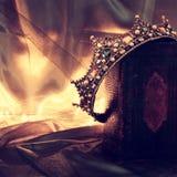 низкое ключевое изображение красивых ферзя/кроны короля на старой книге период фантазии средневековый Стоковое Изображение