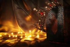 низкое ключевое изображение красивых ферзя/кроны короля на старой книге период фантазии средневековый Стоковое Изображение RF