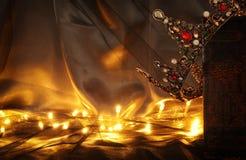 низкое ключевое изображение красивых ферзя/кроны короля на старой книге период фантазии средневековый Стоковые Фотографии RF