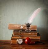 Низкое ключевое изображение белого пера, чернильницы, перечисляет старые книги на старом деревянном столе Стоковое Изображение RF