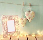 Низкое ключевое изображение винтажной розовой классической рамки, сердца ткани вися на веревочке и фонарик с светами гирлянды, на Стоковое Фото