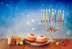 Низкое ключевое изображение еврейского праздника Хануки с menorah, донутами и деревянными dreidels (закручивая верхняя часть) рет