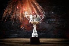 низкое ключевое изображение трофея над деревянным столом и предпосылкой темноты, с абстрактными фейерверками Стоковое Изображение