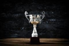 Низкое ключевое изображение трофея над деревянным столом и предпосылкой темноты Стоковая Фотография RF