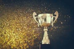 Низкое ключевое изображение трофея над деревянным столом и предпосылкой темноты Стоковое Изображение