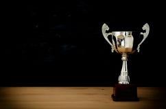 Низкое ключевое изображение трофея над деревянным столом и предпосылкой темноты Стоковые Изображения RF