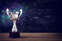 Низкое ключевое изображение трофея над деревянным столом и предпосылкой темноты Стоковое фото RF