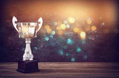 Низкое ключевое изображение трофея над деревянным столом и предпосылкой темноты Стоковые Изображения