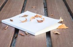 Низкое ключевое фото старой белой книги на деревянном столе с высушенными листьями с темным тоном и выбор фокусируют Стоковые Фото