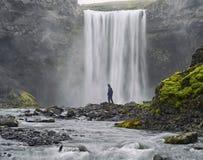 низкопробный черный одетьнный человек положения Исландии снял skogafoss стоя водопад Стоковые Изображения RF