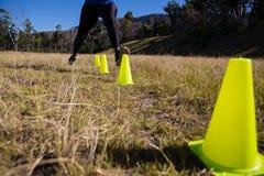 Низко-раздел женщины бежать через конусы тренировки Стоковая Фотография RF