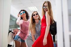 Низко-угол снял стильных блестящих подруг выбирая новые одежды и солнечные очки стоя представляющ перед Стоковые Фото